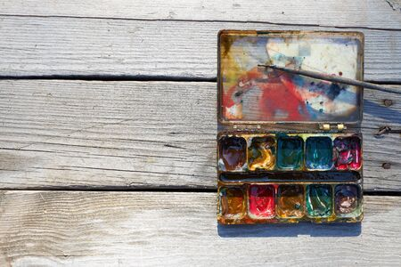 Box with old mixed paints and small brush, copy space. Archivio Fotografico