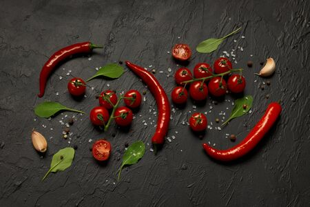 Hot chili peppers pods, cherry tomatoes, garlic, rucola leaves and spices on a black background.
