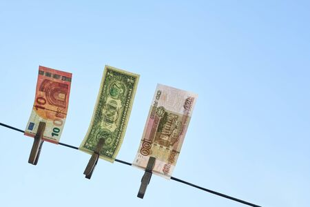 Banknotes of different countries hang on a rope against the blue sky, copy space. Archivio Fotografico - 147467022