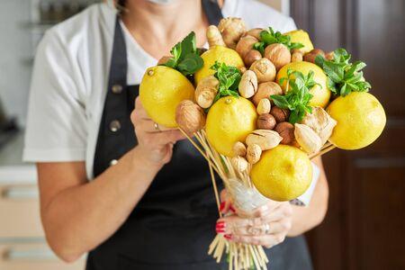 Woman makes a unique fruit bouquet of lemons, nuts and mint.