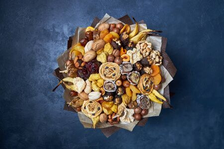 Healthy bouquet of dried fruits and nuts, top view on a dark blue background. Archivio Fotografico