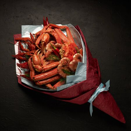 Beautiful unusual packaging of seafood in the form of a bouquet on a black background. Archivio Fotografico