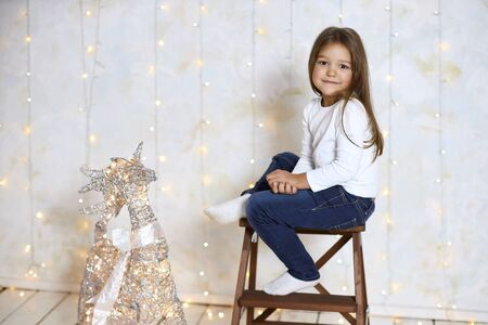 Nice girl with long hair sits on a high chair against a light wall, copy space