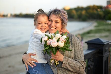 Happy mother and little daughter stand in the evening on the city promenade and laugh