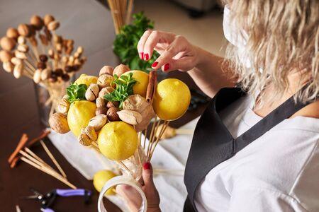 Woman assembles a fruit bouquet of lemons, nuts and mint