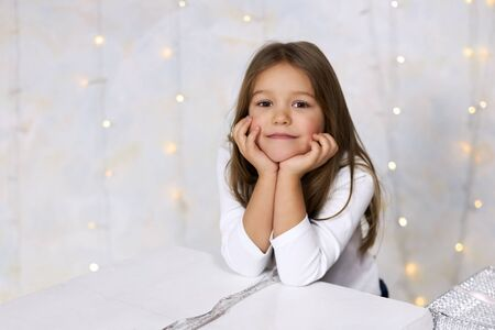 Portrait of a pretty little girl on a light background