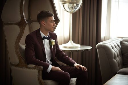 Handsome stylish young man awaiting his bride sitting in a vintage armchair