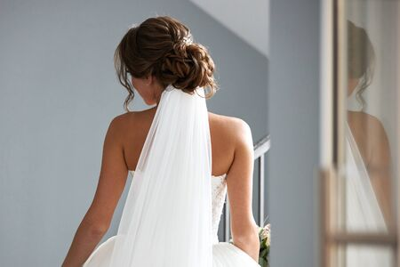 Beautiful bride in a white wedding dress, view from the back