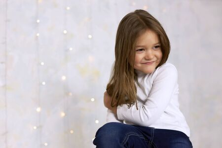 Portrait of a smiling little girl on a light background decorated with garlands
