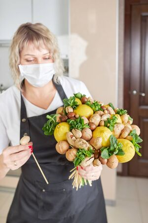 Portrait of a young woman picking a beautiful fruit bouquet of nuts, lemons and mint Archivio Fotografico