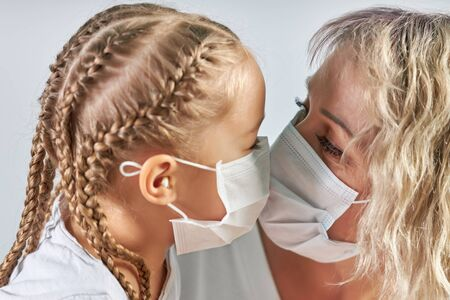 Mother and her daughter kiss in medical masks Archivio Fotografico - 147971669
