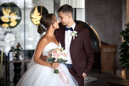 Beautiful bride in a white dress and a handsome groom in a burgundy suit are looking at each other