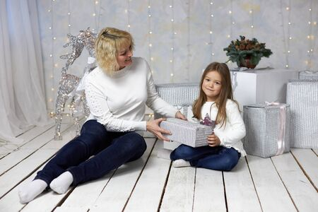 Mom gives her daughter a present on Christmas Eve. Archivio Fotografico - 147971671