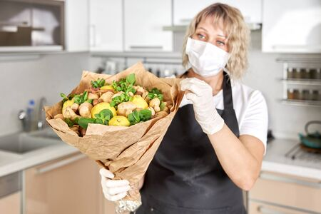 Portrait of a young woman packing the fruit bouquet in wrapping paper