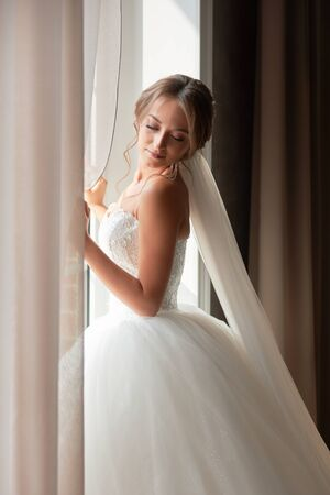 Nice girl in a wedding dress stands at the window