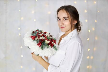 Attractive young woman stands with an original bouquet in her hands on a background of a light wall