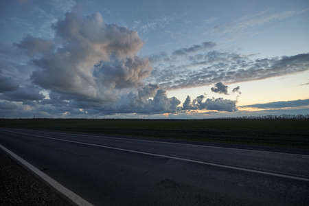 Late evening empty asphalt highway on background of beautiful clouds at sunset.