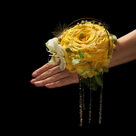 Decoration on wrist of a bride in the form of a large yellow flower.