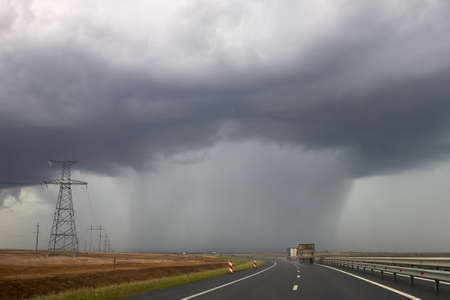 Heavy rain pours from a cloud hanging over the highway.