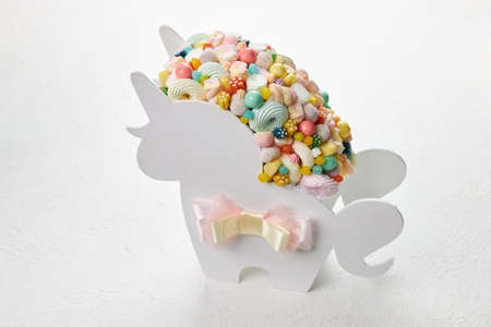Multicolored candy in a white box in the shape of a unicorn on a white background.