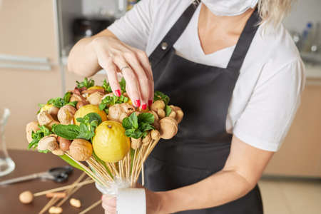 Female designer finishes assembling a fruit bouquet for a gift.