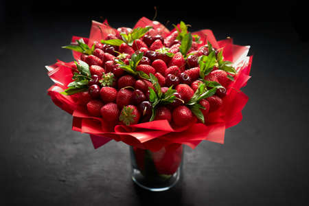 Beautiful bouquet of ripe strawberries and cherries on a black background. Archivio Fotografico