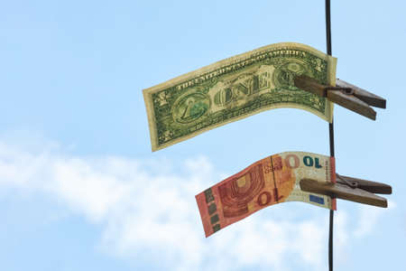 Dollars and euros are hanging on a rope, as a symbol of competition between currencies, concept, copy space.