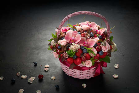 Large basket filled with flowers and fruits on a black background.