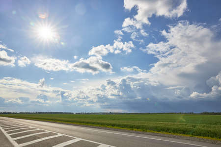 Asphalt highway with road markings on the background of blue sky and clouds.