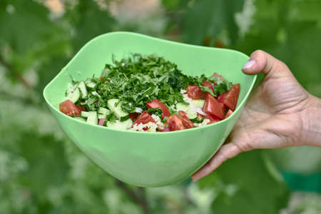 Vegetable salad of tomatoes and cucumbers in a green bowl on a green background.