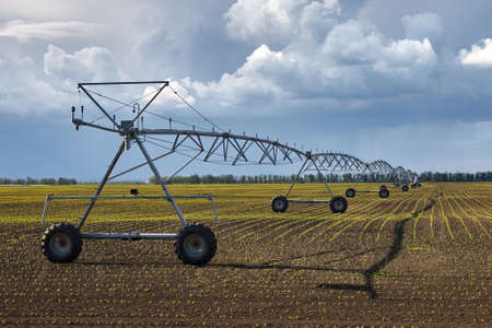 Equipment for automatic irrigation of a large field against a background of blue sky and clouds.