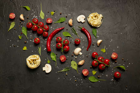Pattern made up of cherry tomatoes, red pepper, garlic, mushrooms, pasta, arugula leaves and spices on a black background. Archivio Fotografico