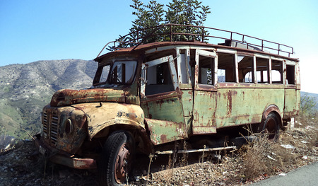 Old rusty abandoned bus on a mountain road