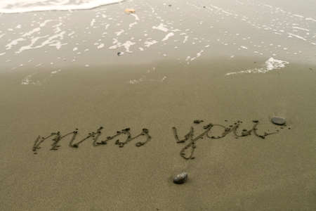 Words Miss You written on wet sand at sea beach