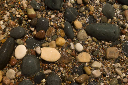Texture of big black stones and small multi colored shining beach pebbles in glittering sea water