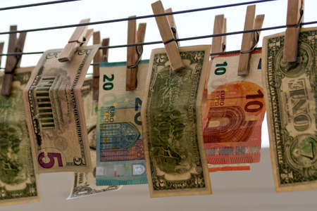 Money laundering concept: Dollar and euro bills hanging out to dry on clotheslines