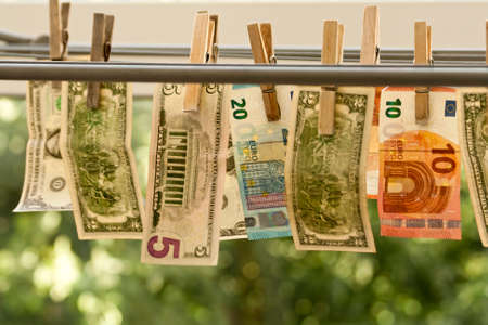 Money laundering concept: Dollar and euro bills hanging out to dry on clotheslines on blurred green background
