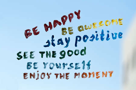 Positive phrases written with different colors on a window glass in front of blue sky