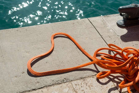 Heart shaped orange rope on concrete ground at sea harbor in sunlight