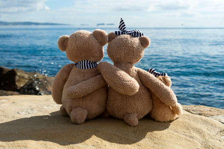 Family of three teddy bears sitting on big white rock and looking at sea and sky