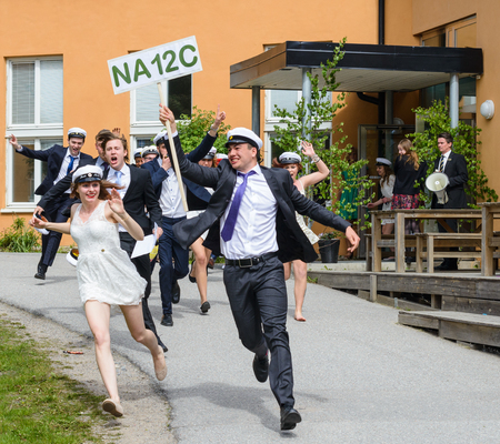 SStockholm, Sweden - June 5, 2015: Group of happy teenagers wearing graduation caps running out from school after graduation from high school at the school, Tullinge Gymnasium Editorial