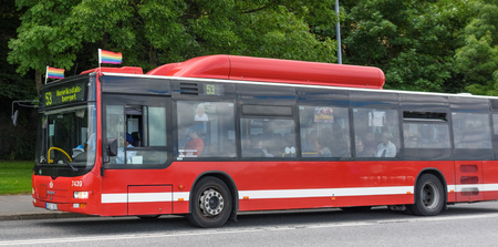 Stockholm, Sweden - July 27, 2015: Red bus in traffic for SL traffic on line 53 with the destination Henriksdalsberget, with pride flags to celebrate the week when Stockholm Pride 2015 takes place in Stockholm, Sweden Stock Photo - 63474445