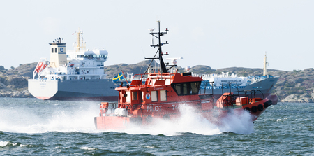 Gothenburg, Sweden - August 29, 2015: Swedish pilot boat, Pilot 746 SE on the way to the ship, M/T TARNBRIS in the port of Gothenburg Stock Photo - 63613197