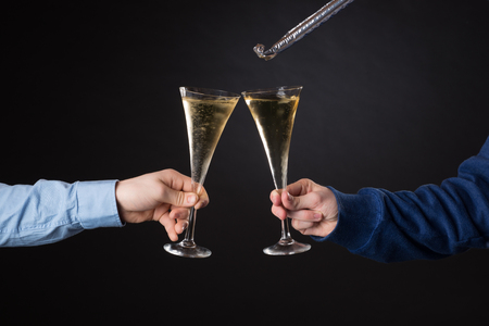 Two male hands holding champagne glasses and foil blowout isolated on black background 스톡 콘텐츠