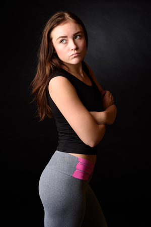 Beautiful girl wearing black and grey fitness outfit isolated on black background