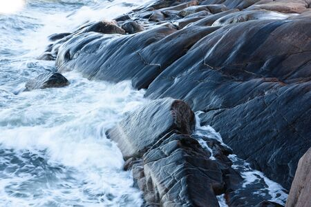 Rolling wave slamming on the rocks of the Finnish coastline Stock Photo - 67959794
