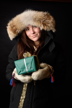 Winter dressed young girl with a Christmas gift isolated on black background