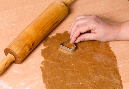 Christmas baking, gingerbread heart cookies with cutter , dough and rolling pin Stock Photo