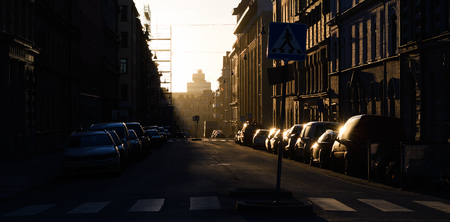 Sunrise early morning, the sun shines on the parked cars in Stockholm, Sweden Stock Photo - 68227574