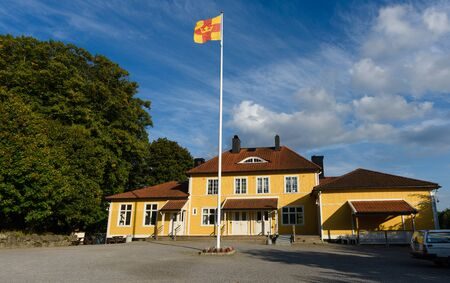 Salem, Sweden - September 11, 2016: Old Church School next to Church of Salem, the sun shines on an autumn day. Flag belonging to the religious community